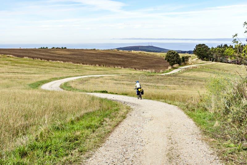 Den kvinnliga cyklisten rider en cykel på en bergig väg till Atlanticet Ocean royaltyfri fotografi
