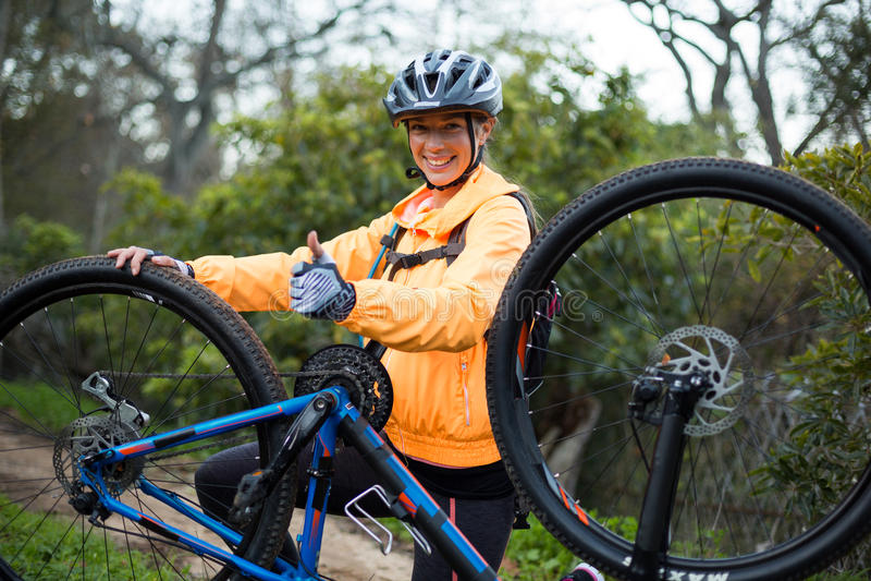 Den kvinnliga cyklistvisningen tummar upp, medan reparera mountainbiket arkivbild