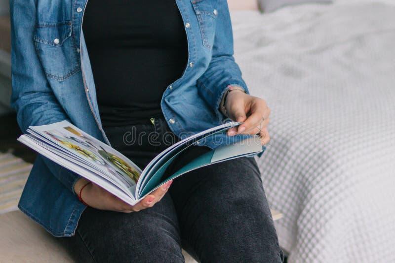 Den kvinnliga deltagaren läser boken på arkivet kunskap Flickan läser en tidskrift tidskrift Rymmer en tidskrift royaltyfri bild