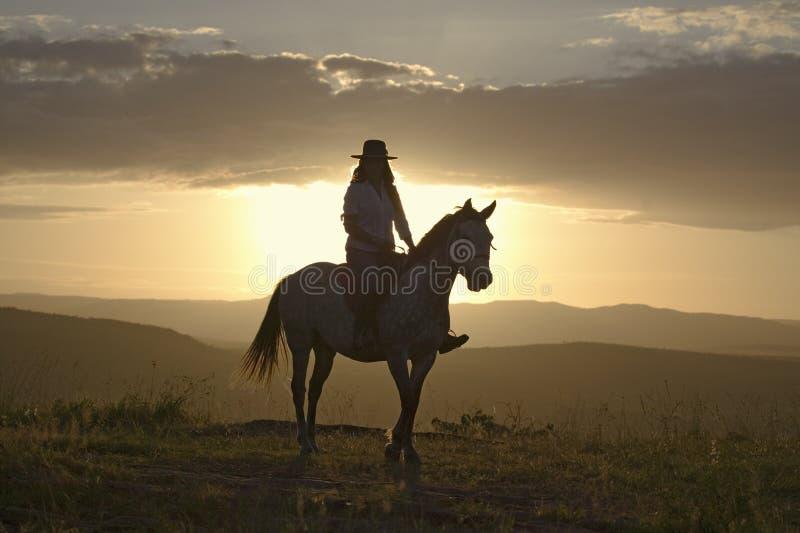 Den kvinnliga den hästryggryttaren och hästen rider för att förbise på Lewa djurlivnaturvård i norr Kenya, Afrika på solnedgången royaltyfri bild