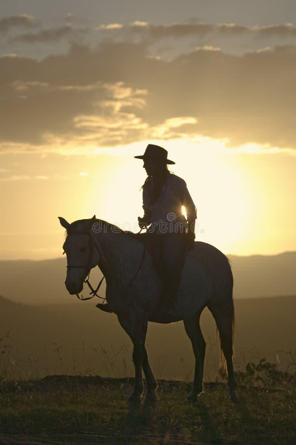 Den kvinnliga den hästryggryttaren och hästen rider för att förbise på Lewa djurlivnaturvård i norr Kenya, Afrika på solnedgången arkivbild