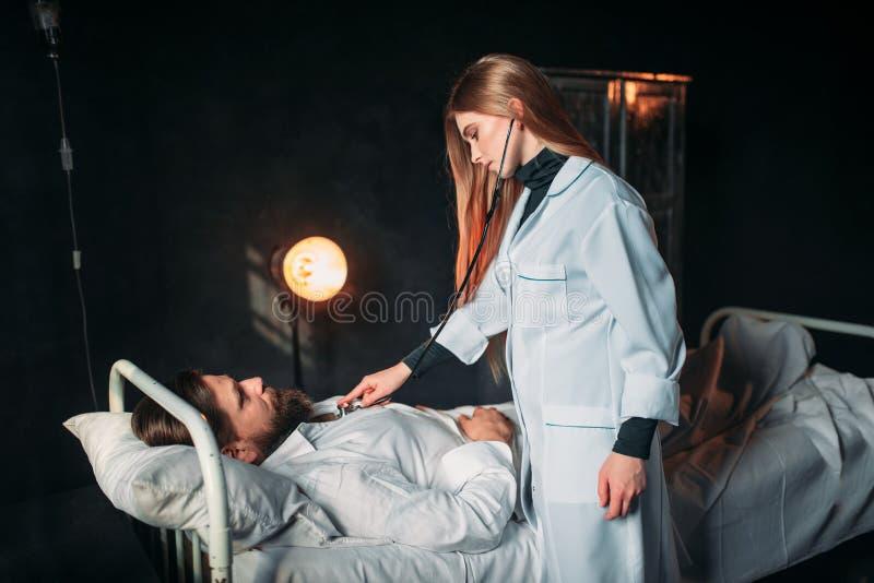 Den kvinnliga doktorn lyssnar till hjärtan av den manliga patienten fotografering för bildbyråer