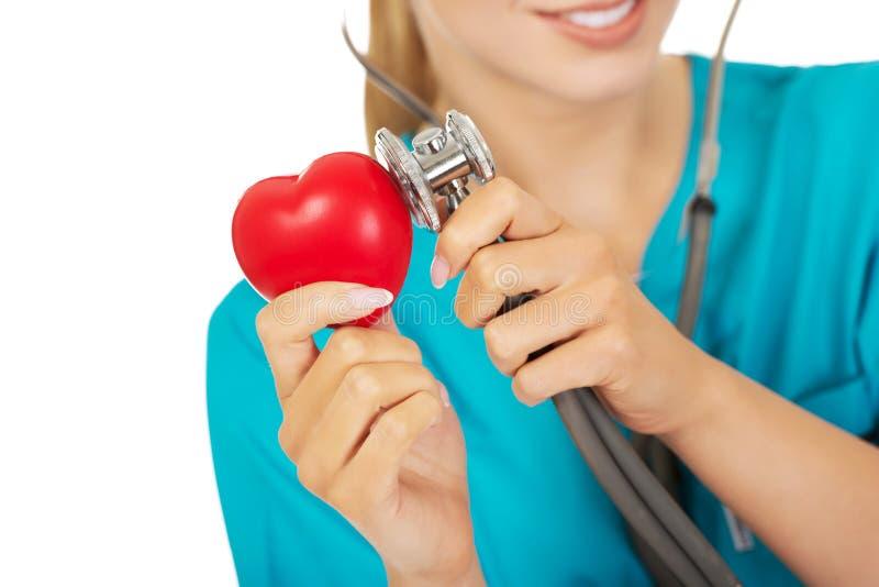 Den kvinnliga doktorn lyssnar till hjärtan till och med en stetoskop arkivbild