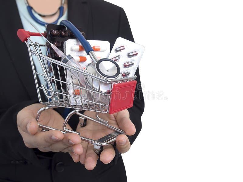 Den kvinnliga doktorn med den svarta dräkten är den hållande lilla shoppingvagnen med färgrika preventivpillerar, injektioninjekt arkivfoton