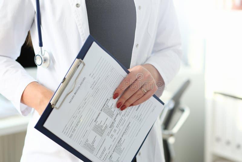 Den kvinnliga doktorn r?cker den rymmande och fyllande patienten royaltyfria foton