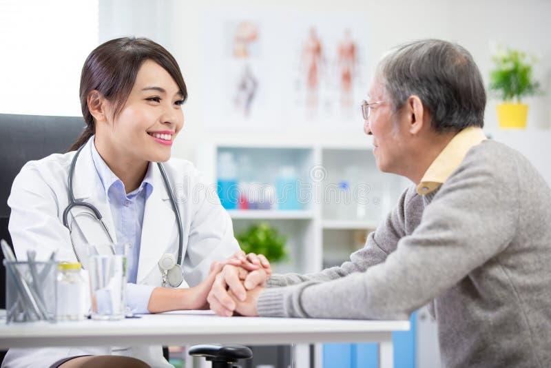 Den kvinnliga doktorn ser äldre patient arkivbild