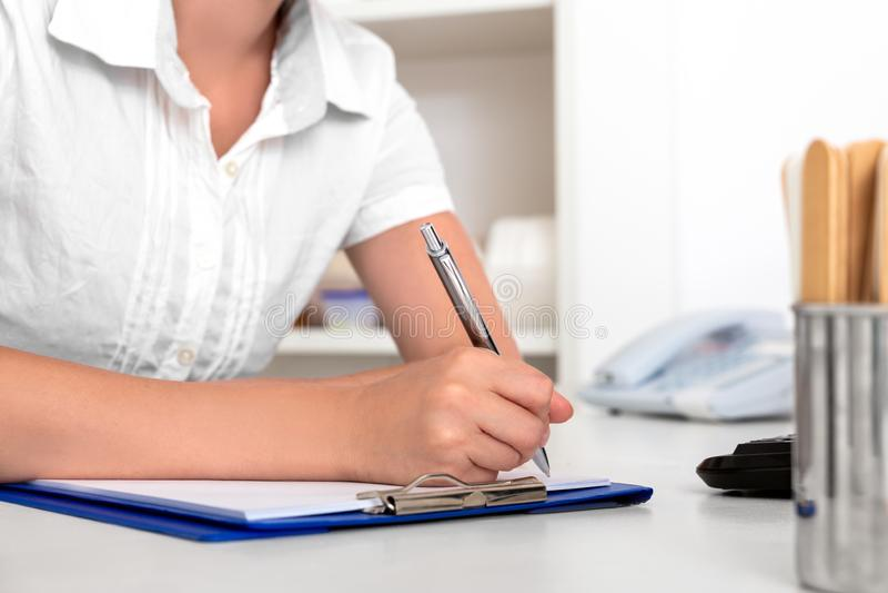 Den kvinnliga doktorn, sjuksköterskan eller sekreteraren gör någon skrivbordsarbete royaltyfria bilder