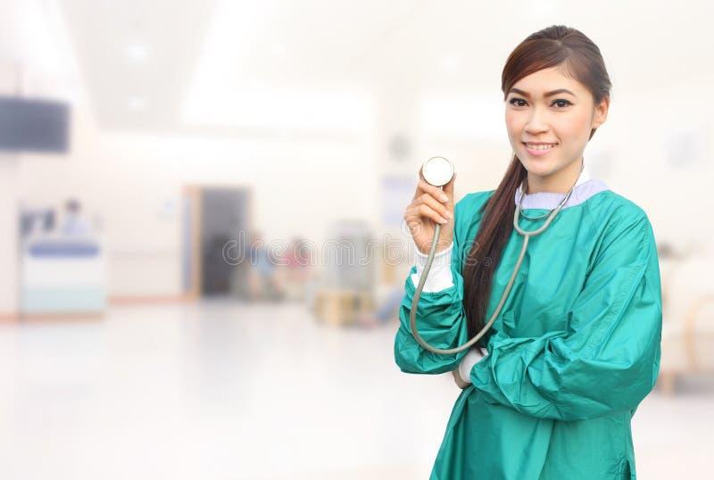 Den kvinnliga doktorn som bär en gräsplan, skurar och stetoskopet i sjukhus arkivbild