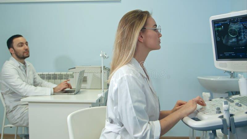 Den kvinnliga doktorn som dikterar ultraljudet, resulterar till hennes manliga kollega med bärbara datorn royaltyfri foto