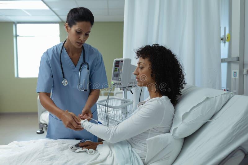 Den kvinnliga doktorn som fäster iv-droppande på den kvinnliga tålmodiga handen i, avvärjer royaltyfri foto