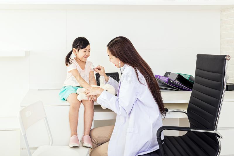 Den kvinnliga doktorn undersöker flickorna Undersökande liten flicka för kvinnlig doktor med stetoskopet doktor för ung kvinna so royaltyfri foto