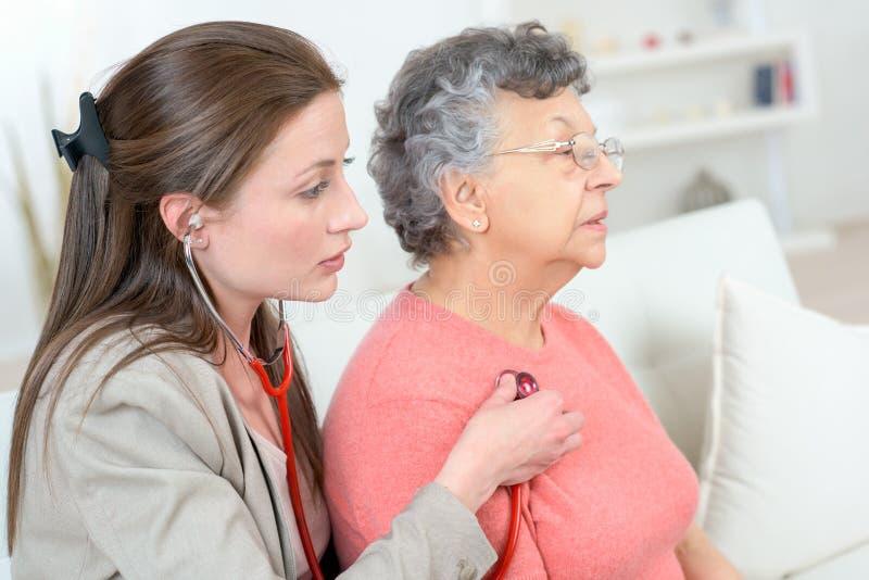 Den kvinnliga doktorn undersöker den höga tålmodiga kvinnan hemma arkivfoto