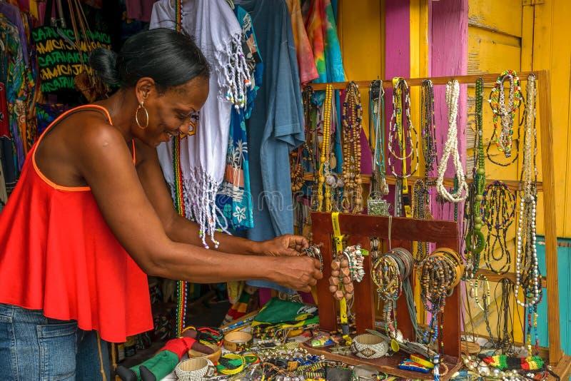 Den kvinnliga försäljaren som säljer pärlkedjor och annan hand - gjorde hantverkobjekt, smycken och kläder en hantverkmarknad royaltyfri fotografi