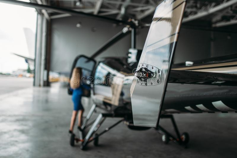 Den kvinnliga flygvärdinnan står mot helikoptern arkivfoton