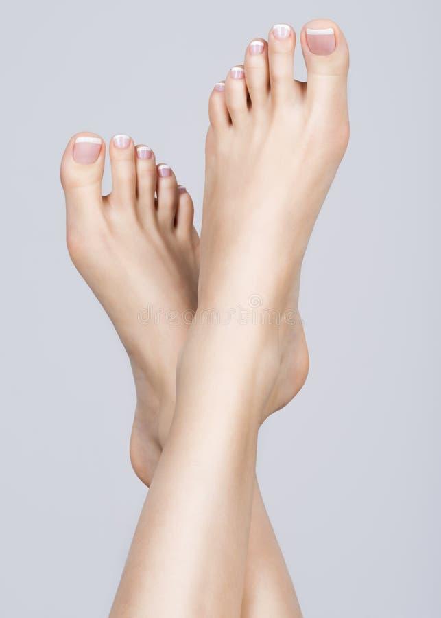 Den kvinnliga foten med den vita franska pedikyren spikar på På brunnsortsalongen arkivbild