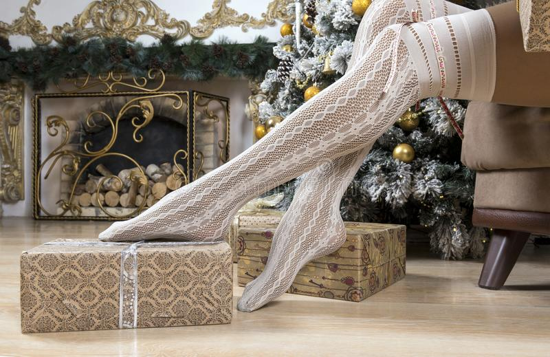 Den kvinnliga foten snör åt in sockor, gåvor i inpackningspapper, jul arkivfoton