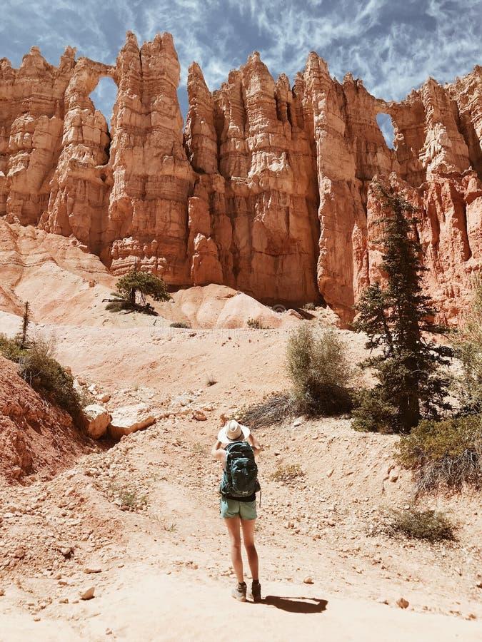 Den kvinnliga fotvandraren i kortslutningar och en sunhat som står av stort, vaggar framme bildande och klippor arkivfoto