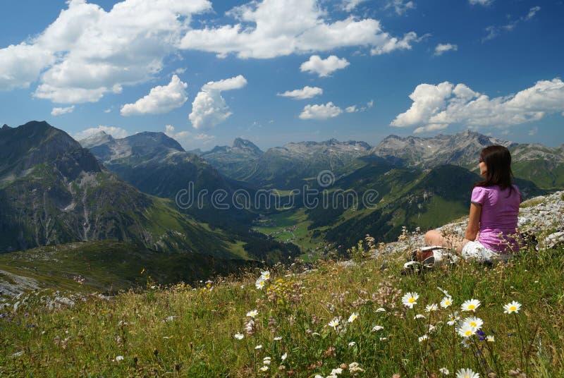 Den kvinnliga fotvandraren tycker om sikten från en alpin äng på den höga höjden royaltyfri bild