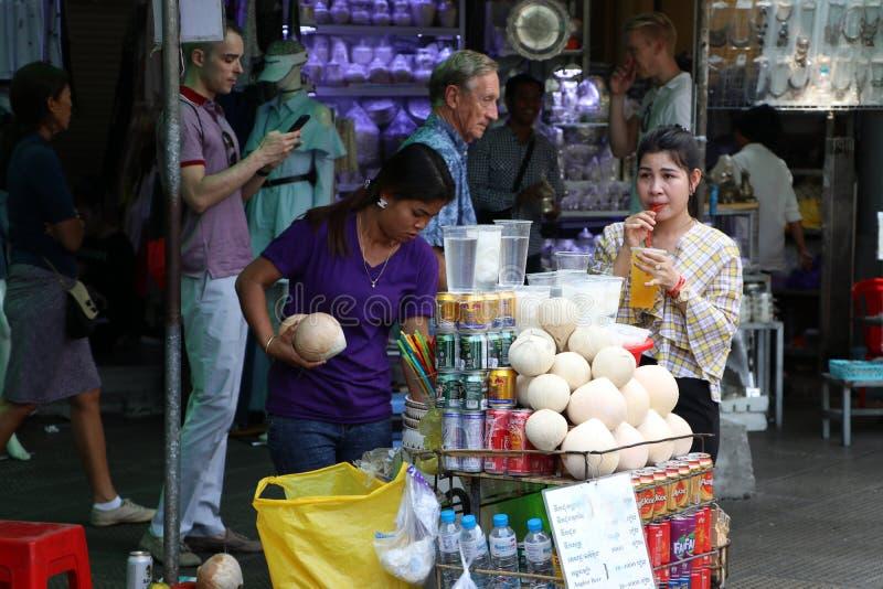 Den kvinnliga gatuförsäljaren som säljer kokosnöten och drycken på den centrala marknaden, en stor marknad med otaligt, stannar a arkivbild
