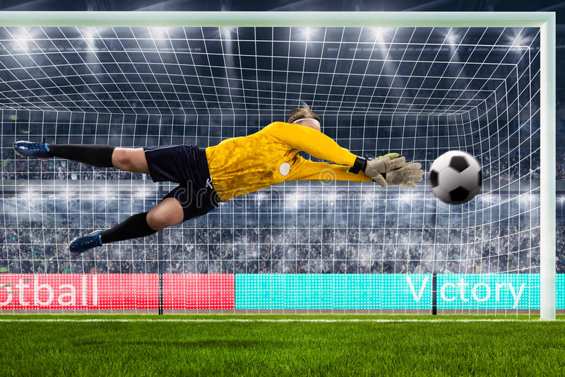 Den kvinnliga goalien hoppar för bollen på fullsatt stadion arkivfoton