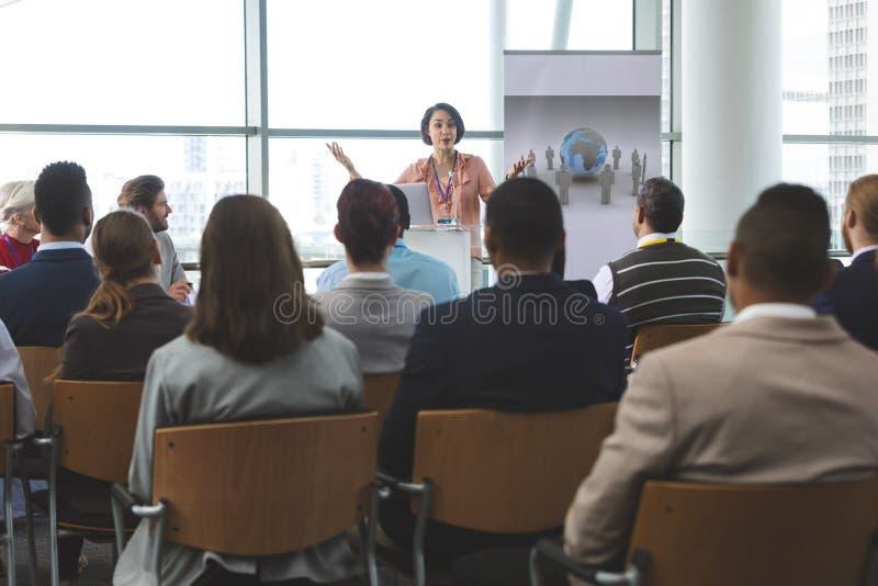 Den kvinnliga högtalaren med bärbara datorn talar i ett affärsseminarium royaltyfri bild