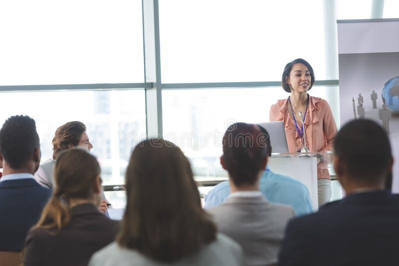 Den kvinnliga högtalaren med bärbara datorn talar i ett affärsseminarium arkivbilder