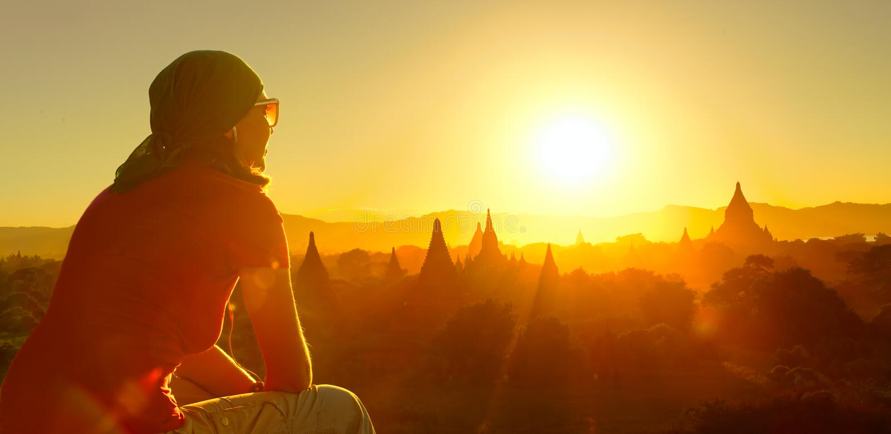 Den kvinnliga handelsresanden kopplar av tempel på Bagan Myanmar Asia på solnedgången arkivbild