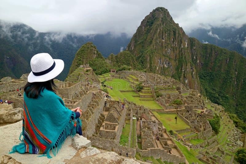 Den kvinnliga handelsresanden som sitter på Cliff Looking på incaen, fördärvar av Machu Picchu, Peru arkivbilder