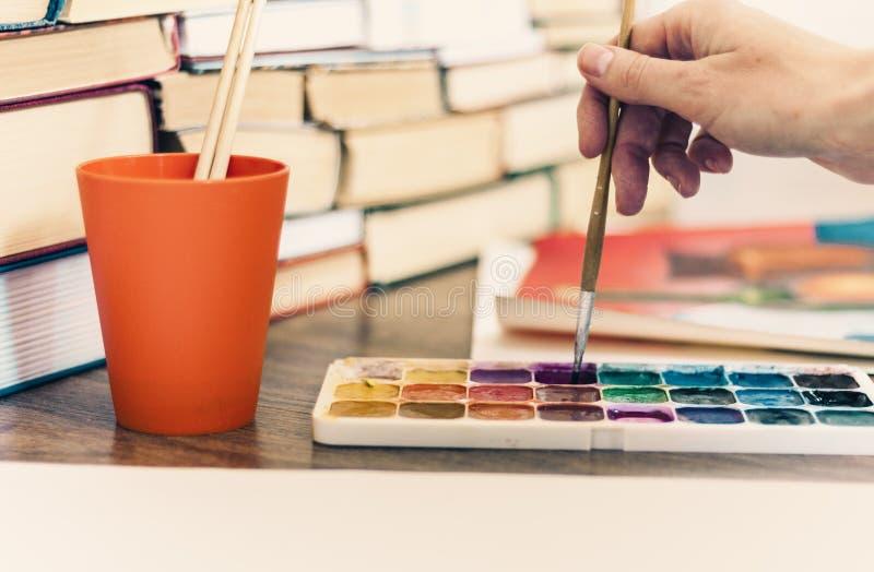 Den kvinnliga handen drar med en borste- och vattenfärgmålarfärg på ett ark av papper på trätabellen med bunten av bokbakgrund royaltyfri fotografi