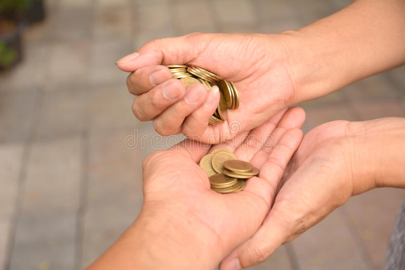 Den kvinnliga handen gömma i handflatan det hällda myntet i gömma i handflatan av manliga händer Kvinnliga mummel arkivbilder