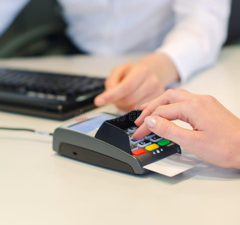 Den kvinnliga handen gör betalning via bankterminalen arkivfoto