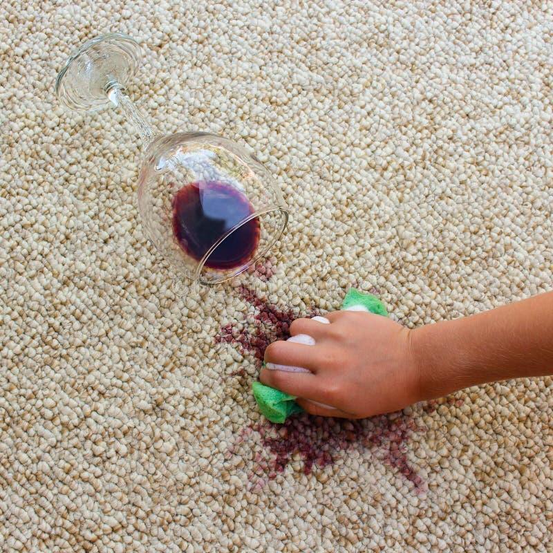 Den kvinnliga handen gör ren mattan med en svamp och ett tvättmedel royaltyfria bilder