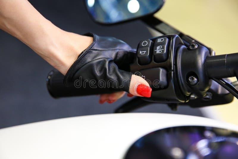 Den kvinnliga handen i en läderhandske trycker på knappen på styret av motorcykeln royaltyfri bild