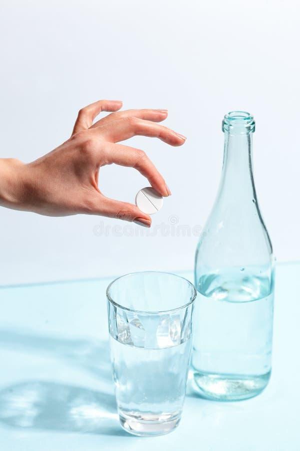 Den kvinnliga handen kastar ett piller in i ett exponeringsglas av vatten Minimalistic begrepp royaltyfria bilder