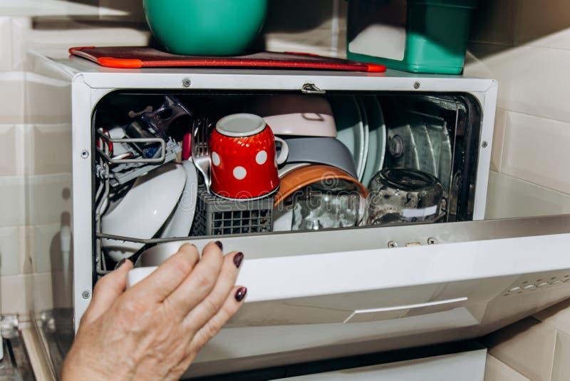 Den kvinnliga handen l?gger disken i en ?ppen diskaren?rbild som stoppas till med ren tv?ttad disk torr bestickcloseup skedgaffla arkivbild