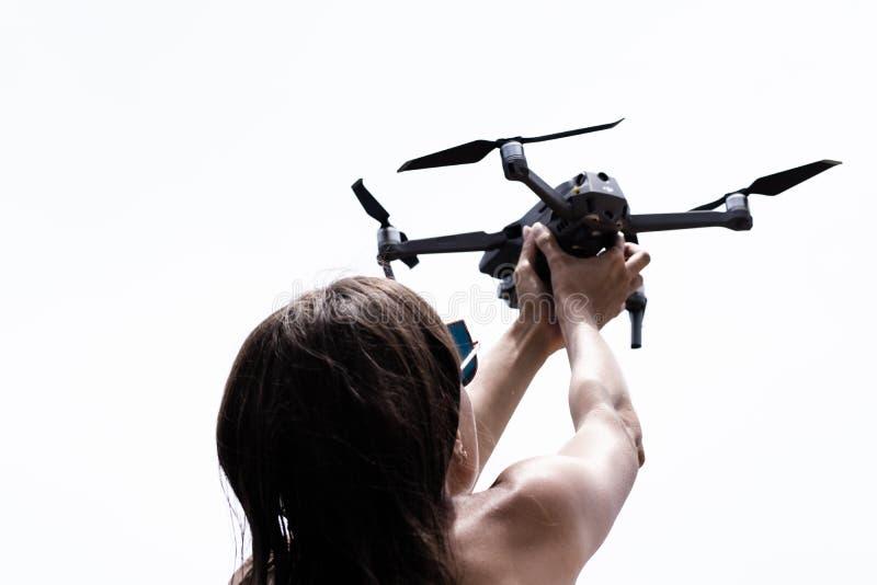 Den kvinnliga handen lanserar surret för flyget, som du kan ta med foto och videofilmande, närbilden arkivbild