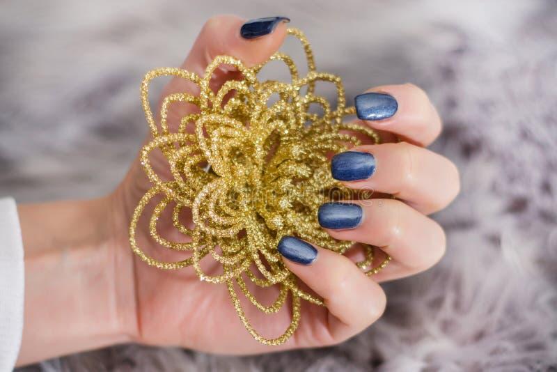 Den kvinnliga handen med marinblått stelnar spikar polerar färg som rymmer den guld- dekorativa blomman royaltyfria foton