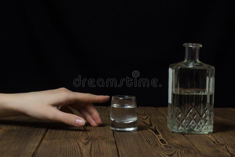 Den kvinnliga handen når för ett exponeringsglas med alkohol, svart bakgrundsalkohol royaltyfria foton