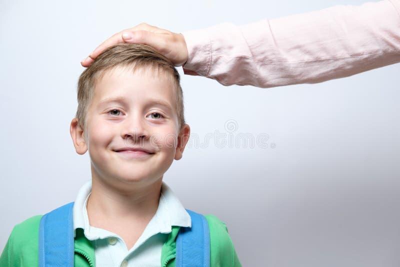 Den kvinnliga handen på huvudet av en gullig skolpojke med blått vandrar på a royaltyfri bild