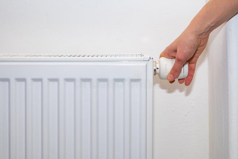 Den kvinnliga handen reglerar termostatknoppen på det vita uppvärmningelementet med hemma en kall säsong arkivfoton