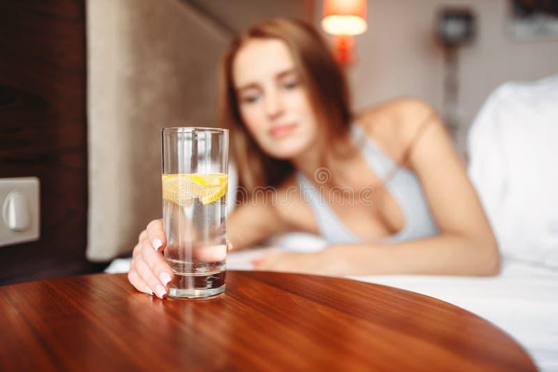Den kvinnliga handen rymmer exponeringsglas med citronvatten arkivbild