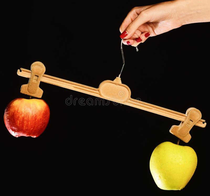 Den kvinnliga handen rymmer hängaren med frukter på spetsar arkivfoto