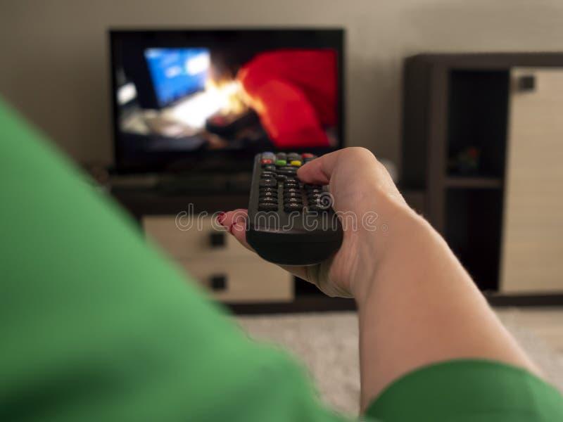 Den kvinnliga handen rymmer TV den avlägsna bakre sikten royaltyfri foto