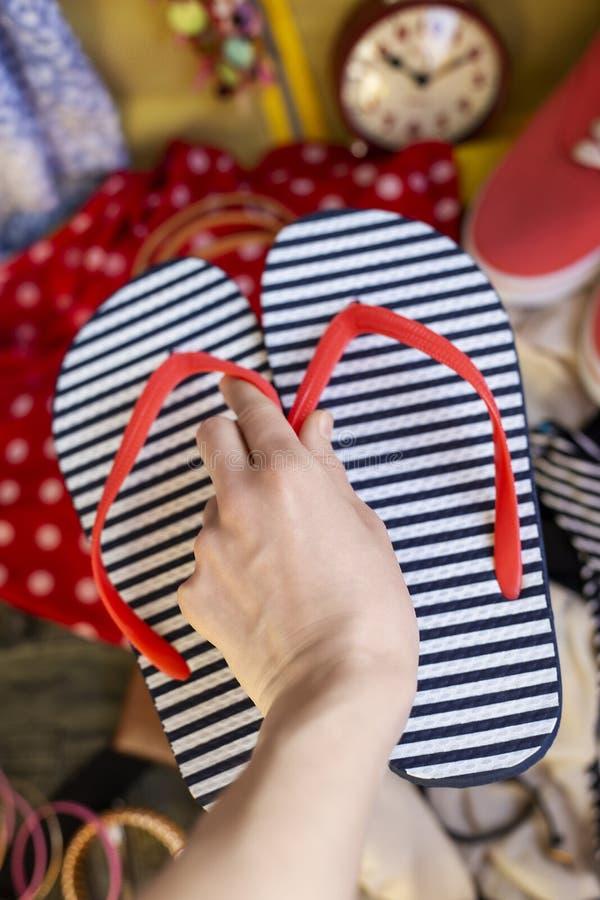 Den kvinnliga handen sätter bläddrar misslyckanden i resväska arkivfoton