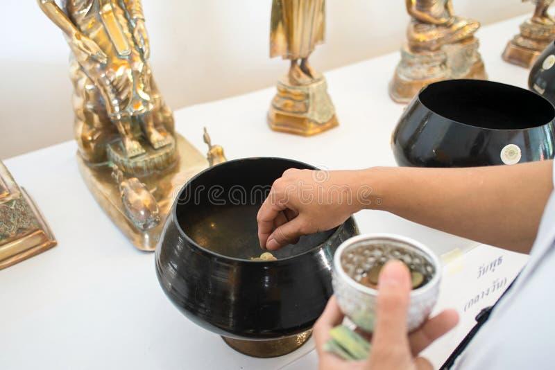 Den kvinnliga handen satte det thai myntet i munk som allmosa bowlar för att göra merit fotografering för bildbyråer