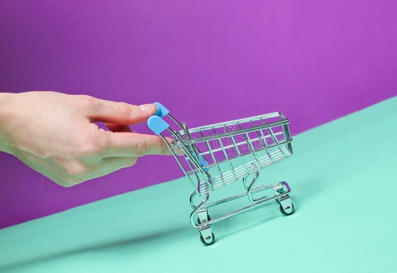 Den kvinnliga handen skjuter upp att slutta den tomma mini- shoppa spårvagnen fotografering för bildbyråer