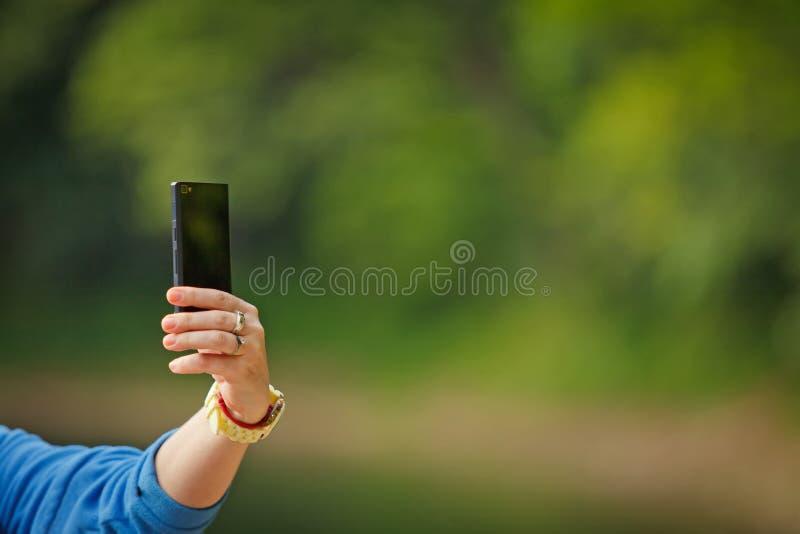 Den kvinnliga handen tar bilder med den smarta telefonen för mobilen fotografering för bildbyråer