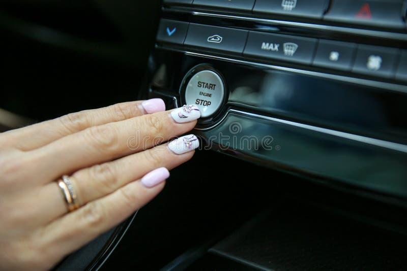 Den kvinnliga handen trycker på upp startknappen motorn i bilslutet royaltyfria bilder
