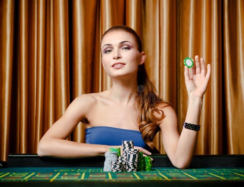 Den kvinnliga hasardspelaren med gå i flisor räcker in på kasinot royaltyfri foto