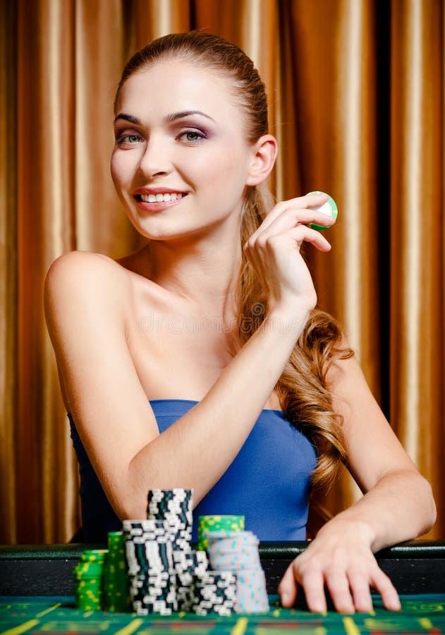 Den kvinnliga hasardspelaren på leka bordlägger royaltyfri foto